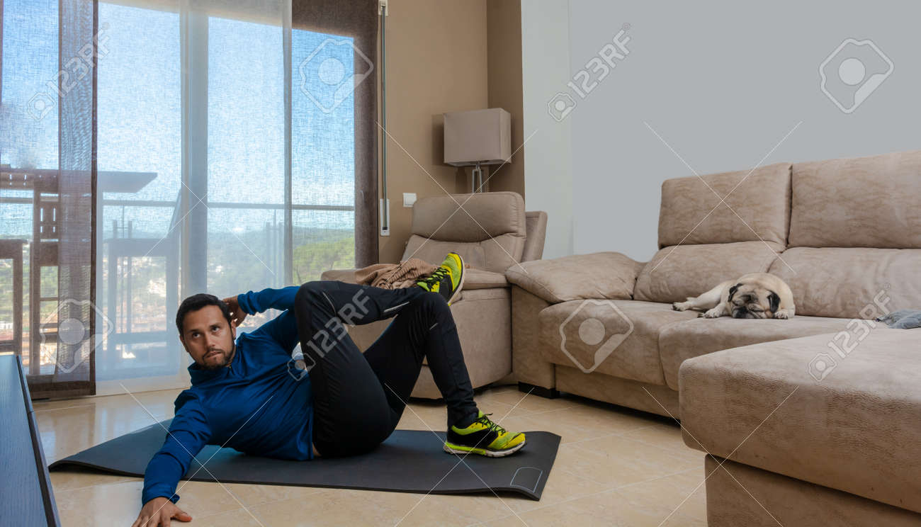 Latin man, doing a workout in his living room, does sit-ups, stretches and squats - 162577861