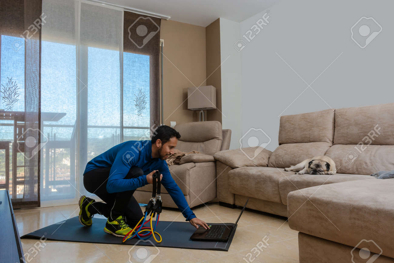 Latin man, doing a workout in his living room with a rubber band while taking an online class - 162577865