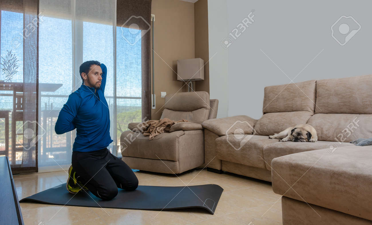 Latin man, doing a workout in his living room, does sit-ups, stretches and squats - 162577866