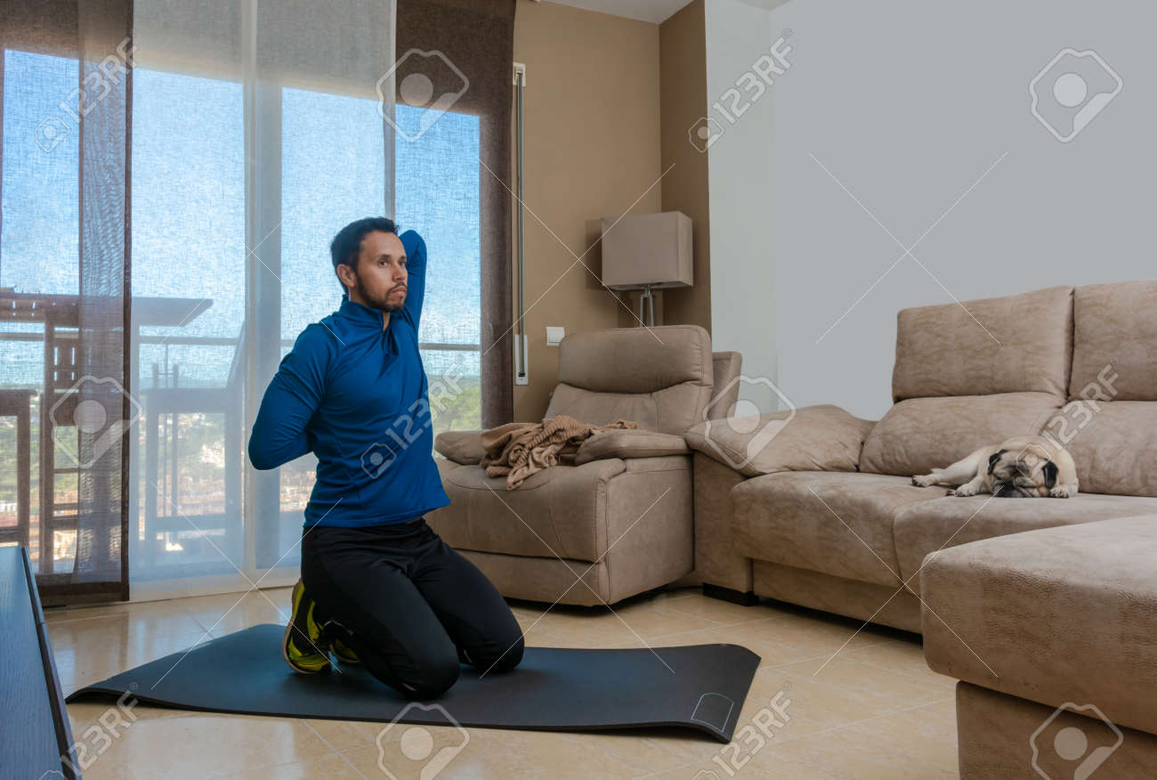 Latin man, doing a workout in his living room with a rubber band while taking an online class - 159523026