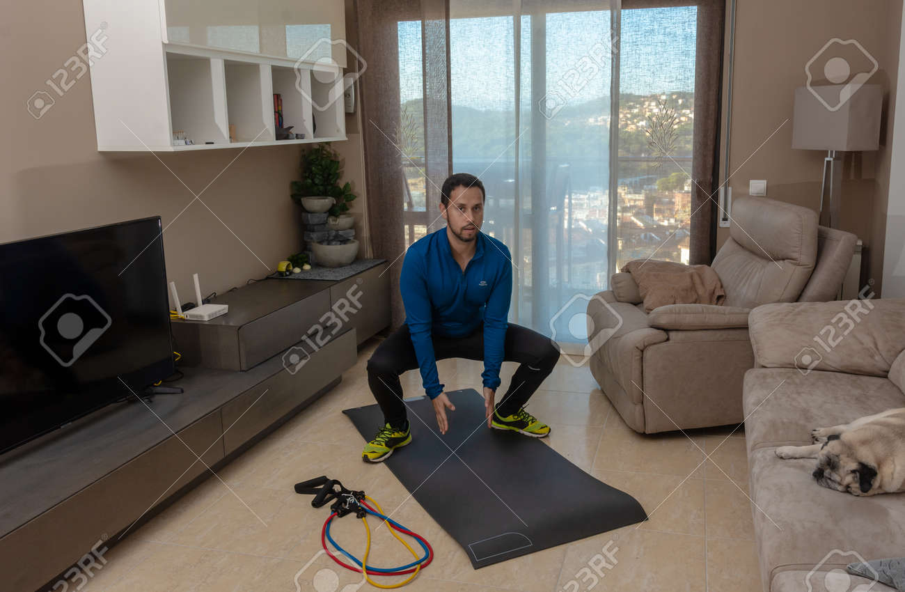 Latin man, doing a workout in his living room with a rubber band while taking an online class - 159523264