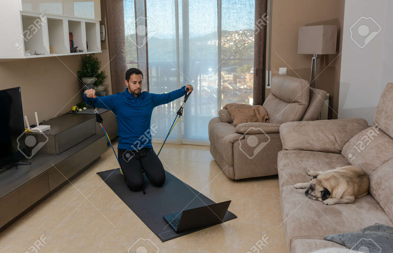 Latin man, doing a workout in his living room with a rubber band while taking an online class - 159523019