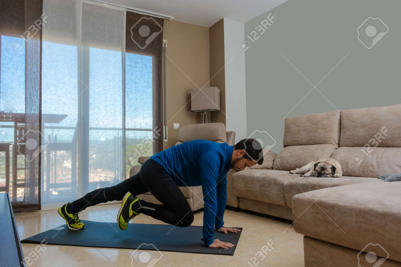 Latin man, doing a workout in his living room with a rubber band while taking an online class - 159523415
