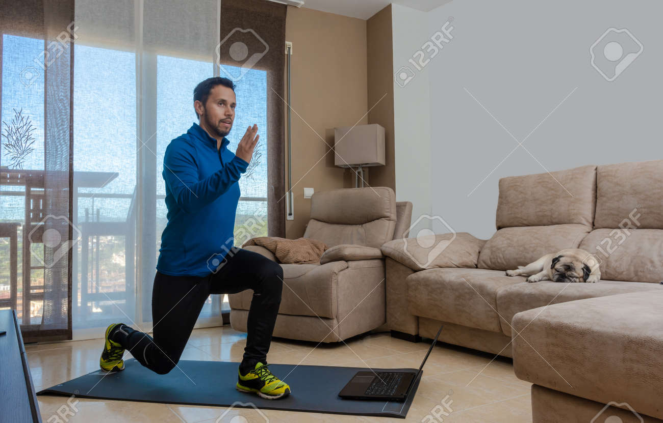 Latin man, doing a workout in his living room with a rubber band while taking an online class - 159523036