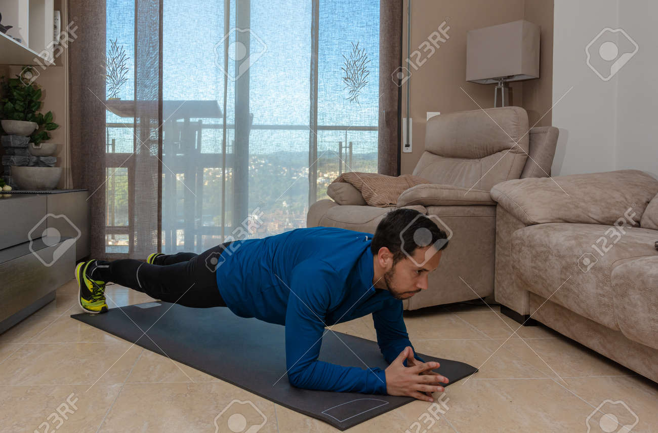 Latin man, doing a workout in his living room with a rubber band while taking an online class - 159523069