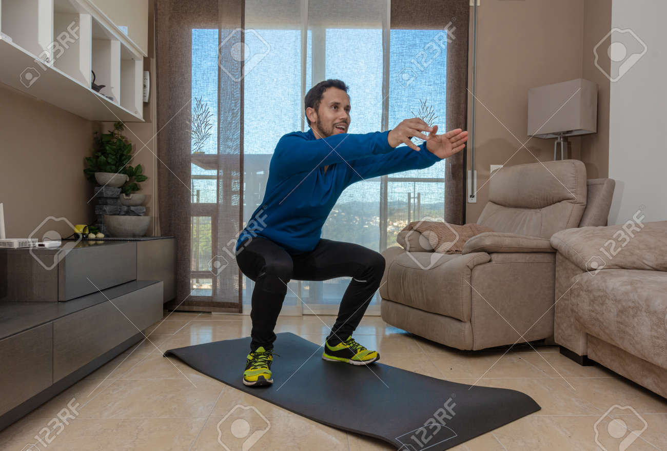 Latin man, doing a workout in his living room with a rubber band while taking an online class - 159523056