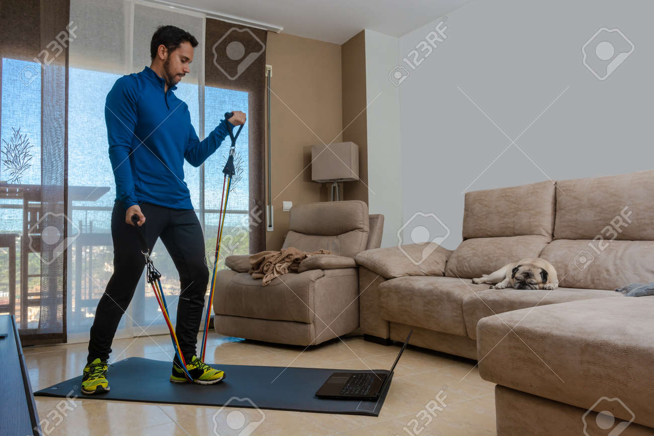 Latin man, doing a workout in his living room with a rubber band while taking an online class - 162578107