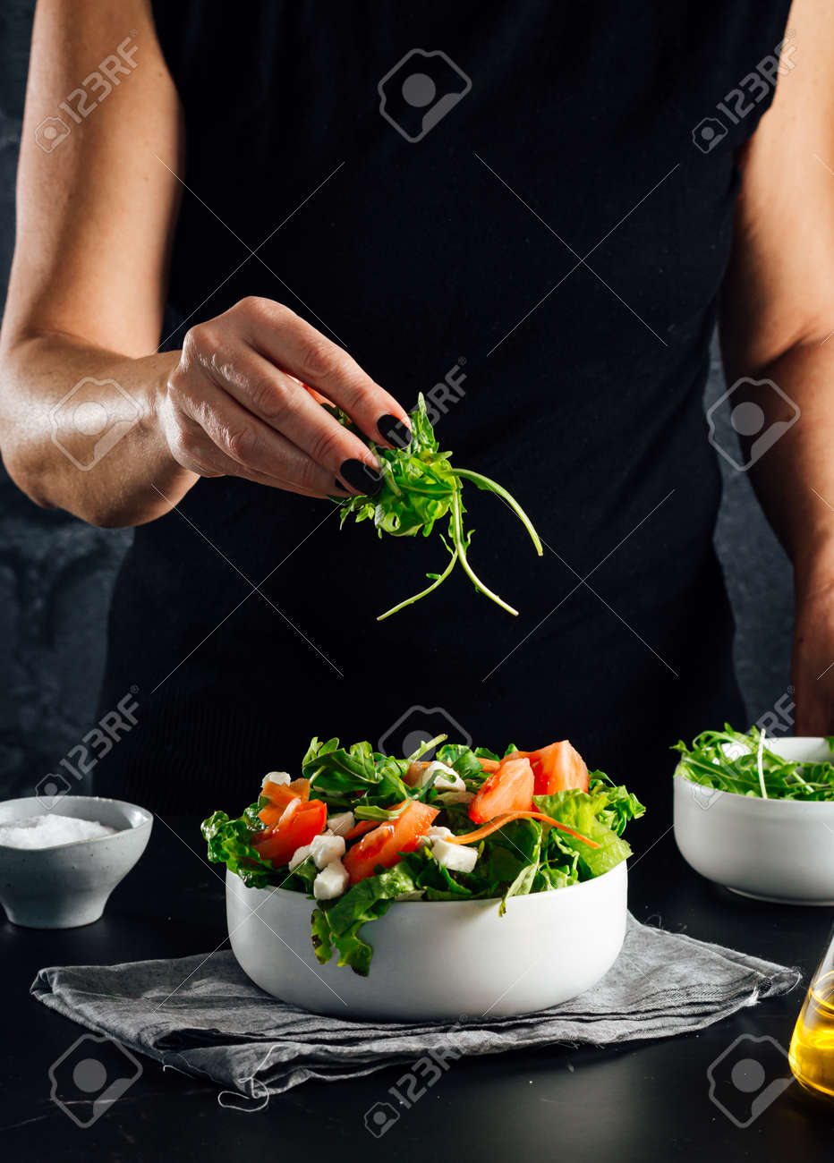 Woman preparing a salad with tomatoes, lettuce, olive oil and salt Concept of healthy diet - 165273810