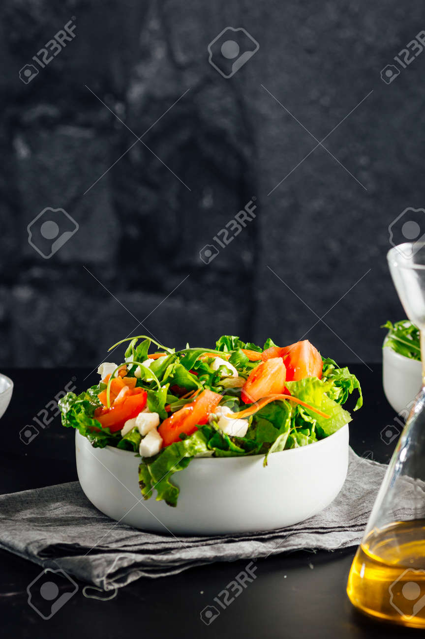 Mixed salad bowl with lettuce, tomato, arugula and mozzarella cheese. (Concept of healthy and organic food) - 165273812