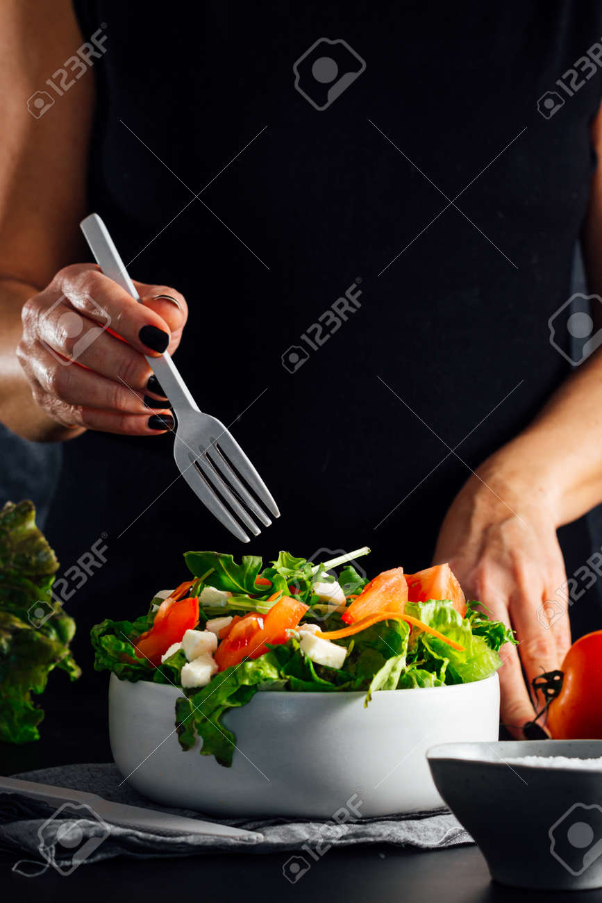 Woman preparing a salad with tomatoes, lettuce, olive oil and salt Concept of healthy diet - 165273816