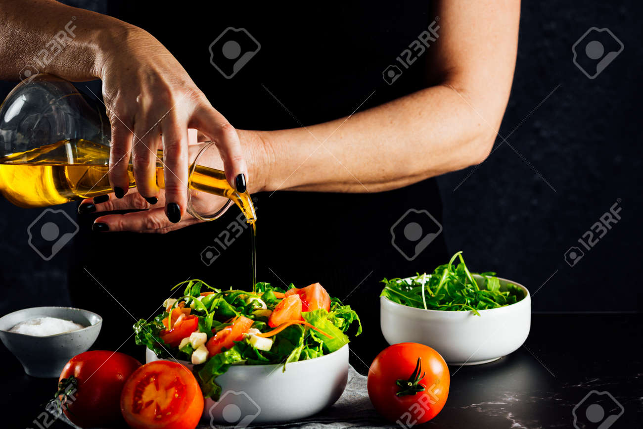 Woman preparing a salad with tomatoes, lettuce, olive oil and salt Concept of healthy diet - 165273817