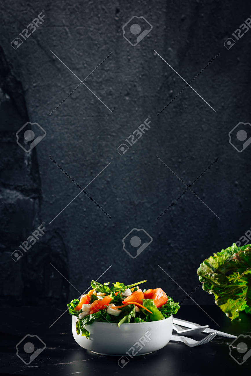 Mixed salad bowl with lettuce, tomato, arugula and mozzarella cheese. (Concept of healthy and organic food) - 165273821