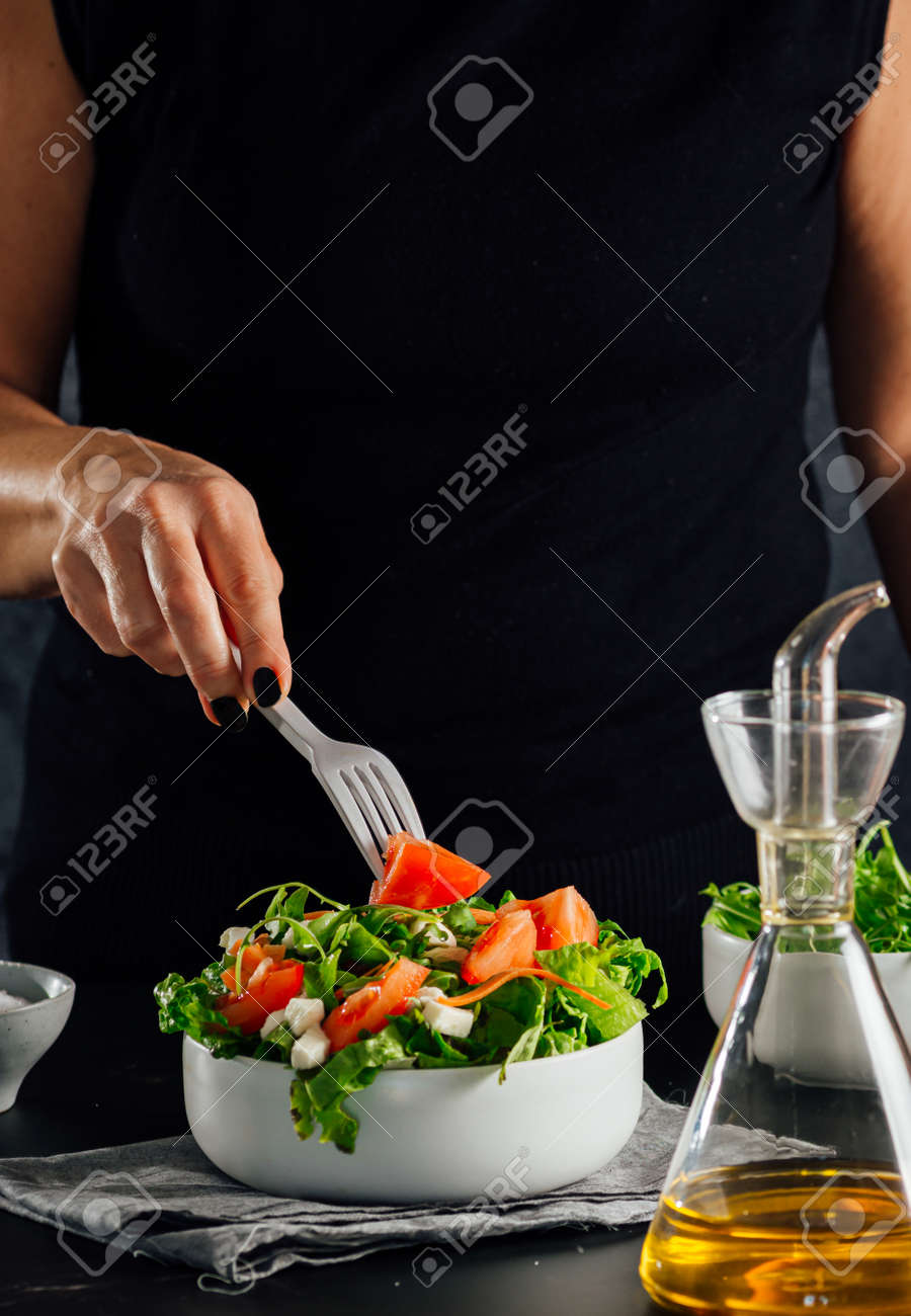 Woman preparing a salad with tomatoes, lettuce, olive oil and salt Concept of healthy diet - 165273826