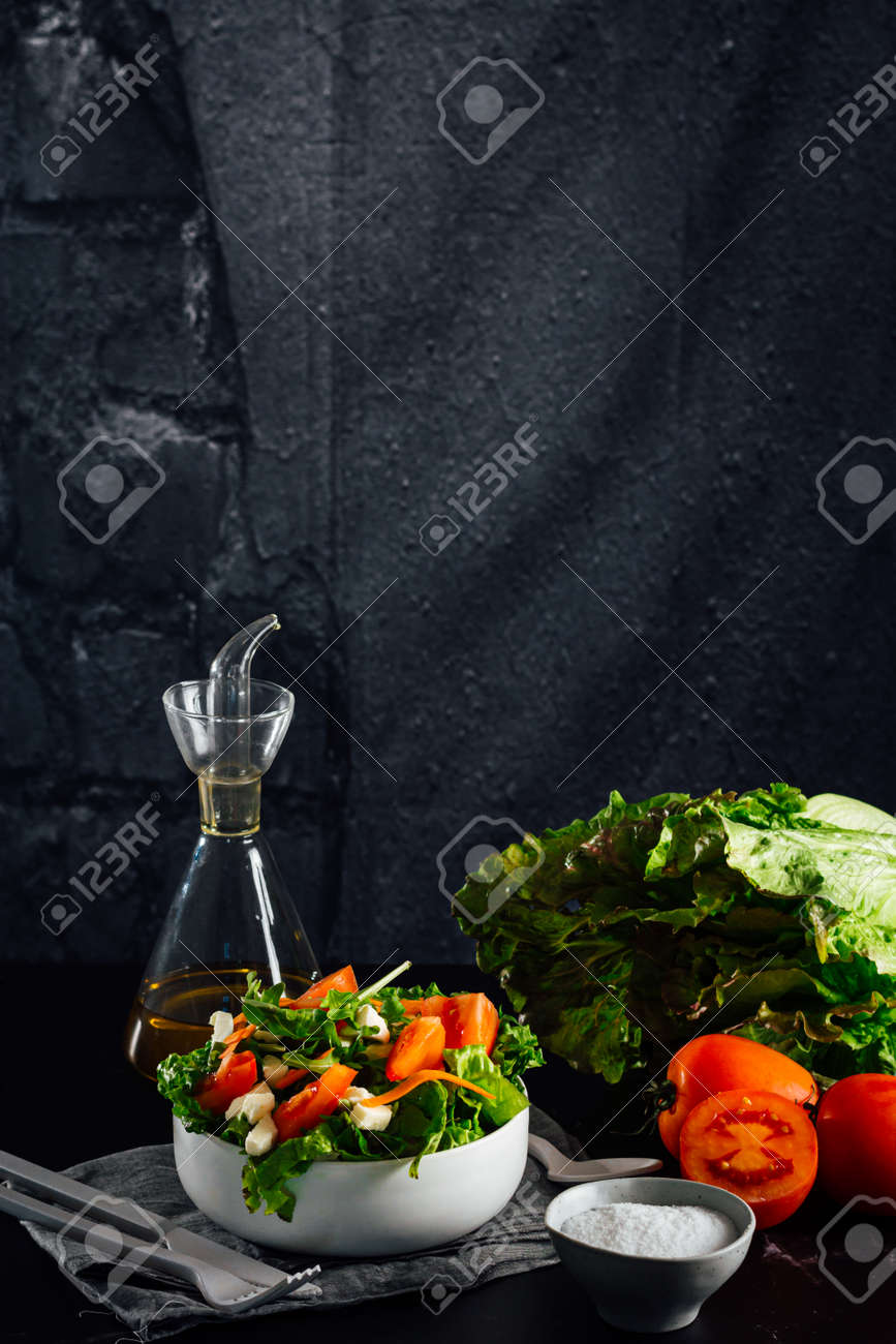 Mixed salad bowl with lettuce, tomato, arugula and mozzarella cheese. (Concept of healthy and organic food) - 165273827