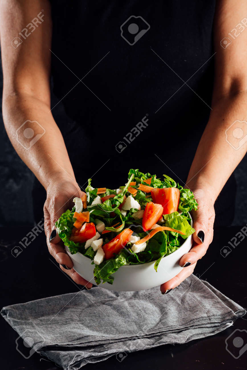 Woman preparing a salad with tomatoes, lettuce, olive oil and salt Concept of healthy diet - 165273828