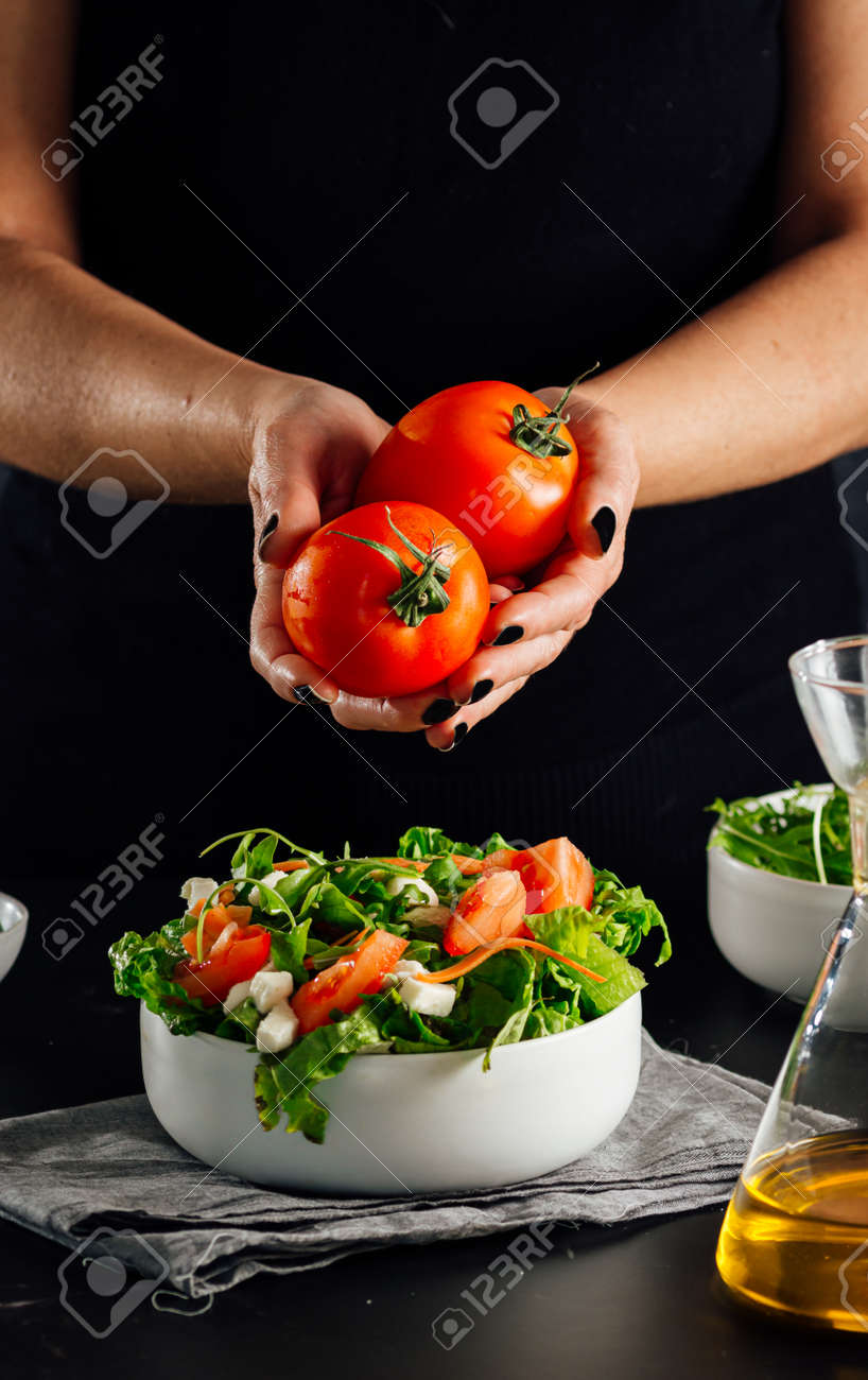 Woman holding a couple of tomatoes to add them to the salad to be eaten (Healthy and fit diet concept) - 165273829