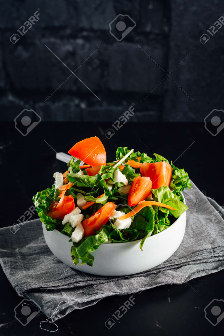 Mixed salad bowl with lettuce, tomato, arugula and mozzarella cheese. (Concept of healthy and organic food) - 165273830