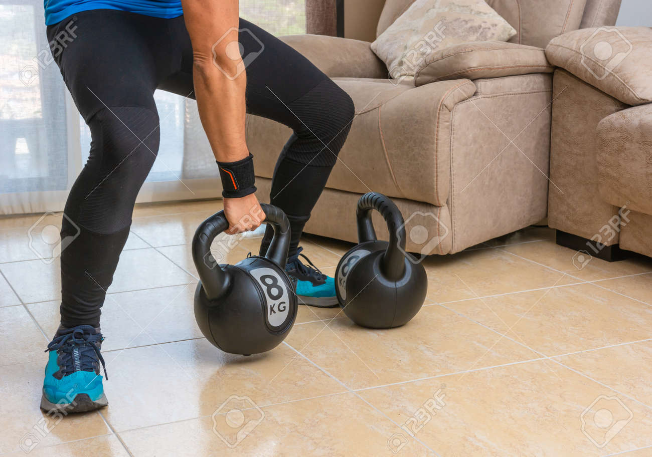 Latin man performing a cross fit workout at home with a pair of kettlebells. - 169767901