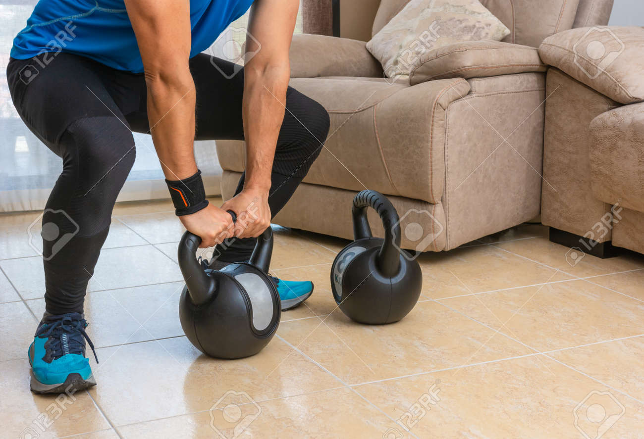 Latin man performing a cross fit workout at home with a pair of kettlebells. - 169767962