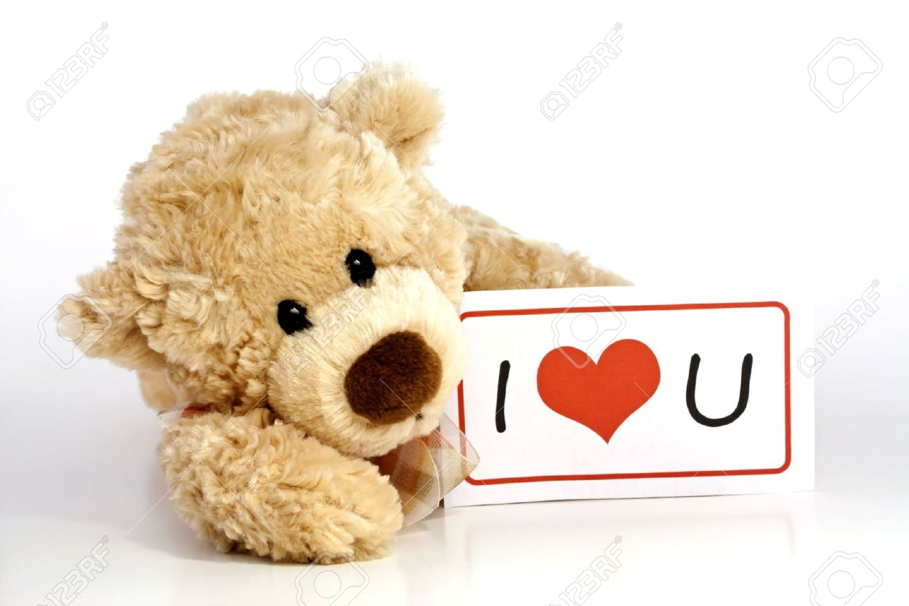 cute furry brown teddy bear laying down holding an i love you