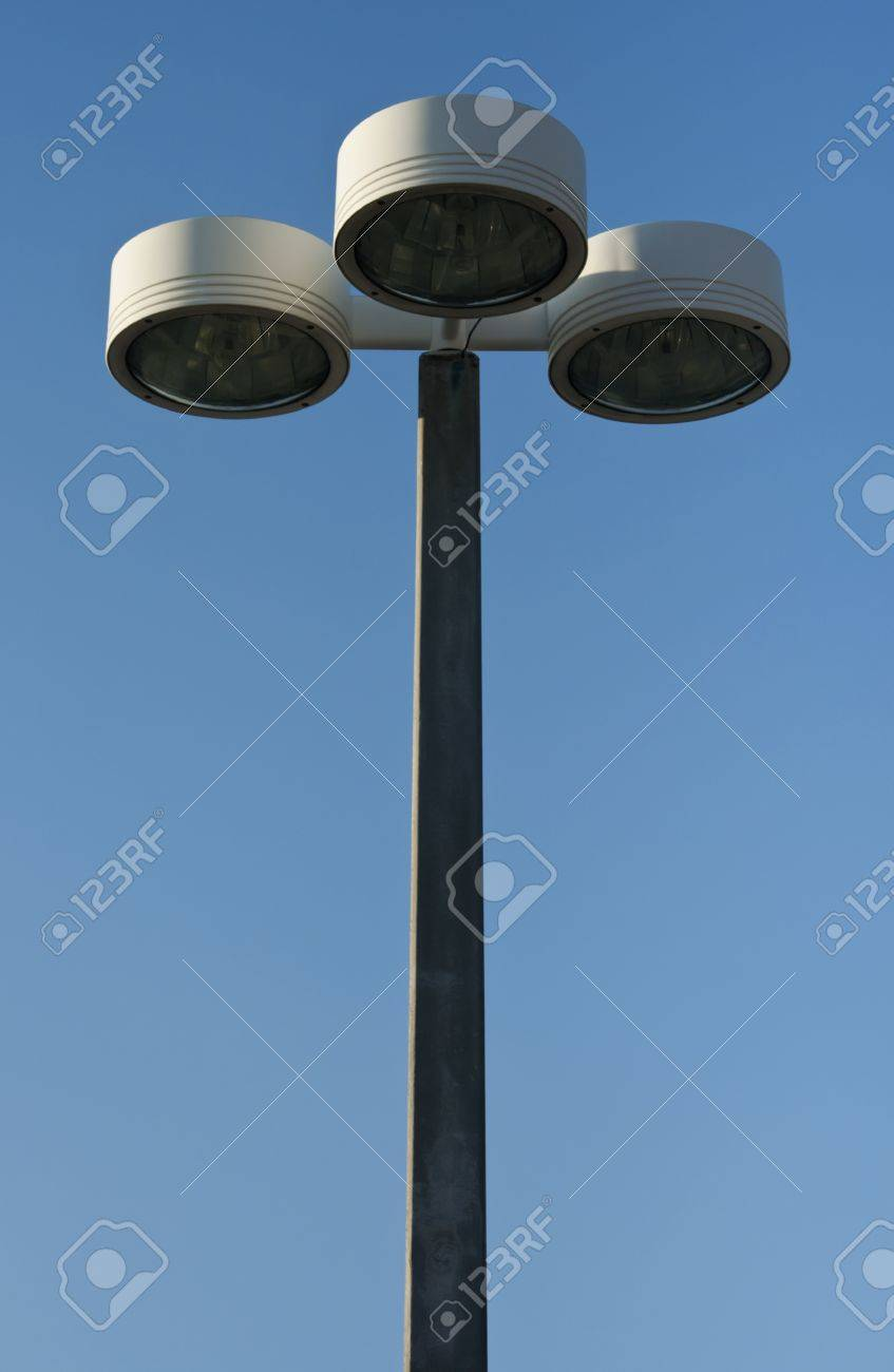 Centered Outdoor Lamp Post Or Light Pole With Three Lamp Heads Against  Bright Blue Sky With