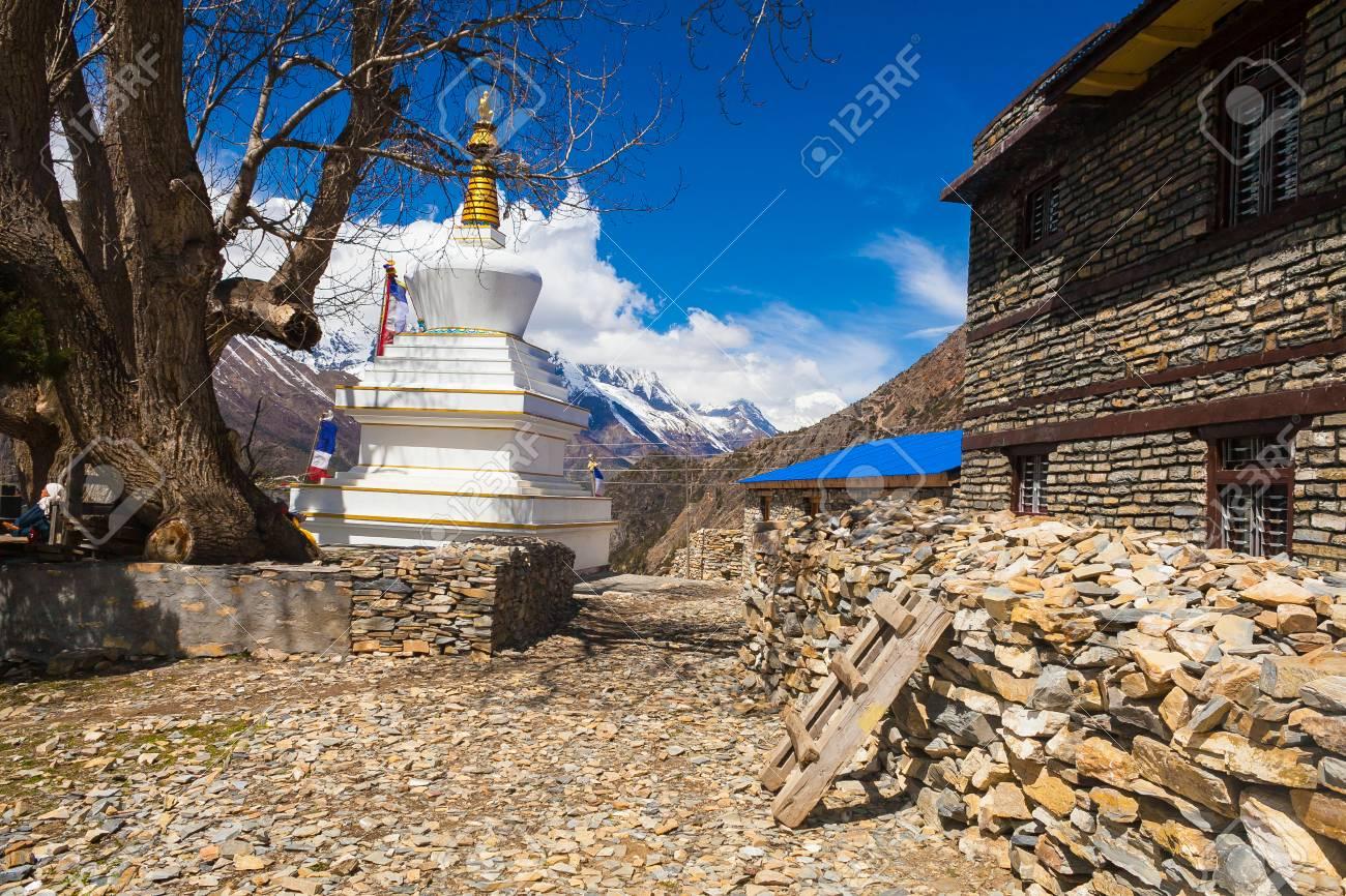 Tibetan prayer stupa or prayers place of the faithful Buddhists in center Mountains Village. Blue Sky Background. Horizontal photo Stock Photo - 63727181