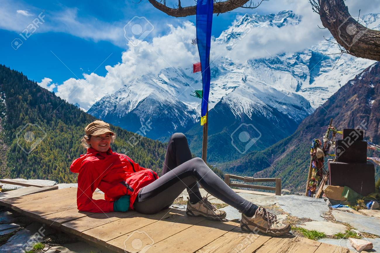 Beautiful Woman Traveler Backpacker Take Rest Mountain Terrace Village.Young Girl Posing Smiling Camera.North Snow Peaks Landscape Background. Cloudy Sky Stock Photo - 63727210