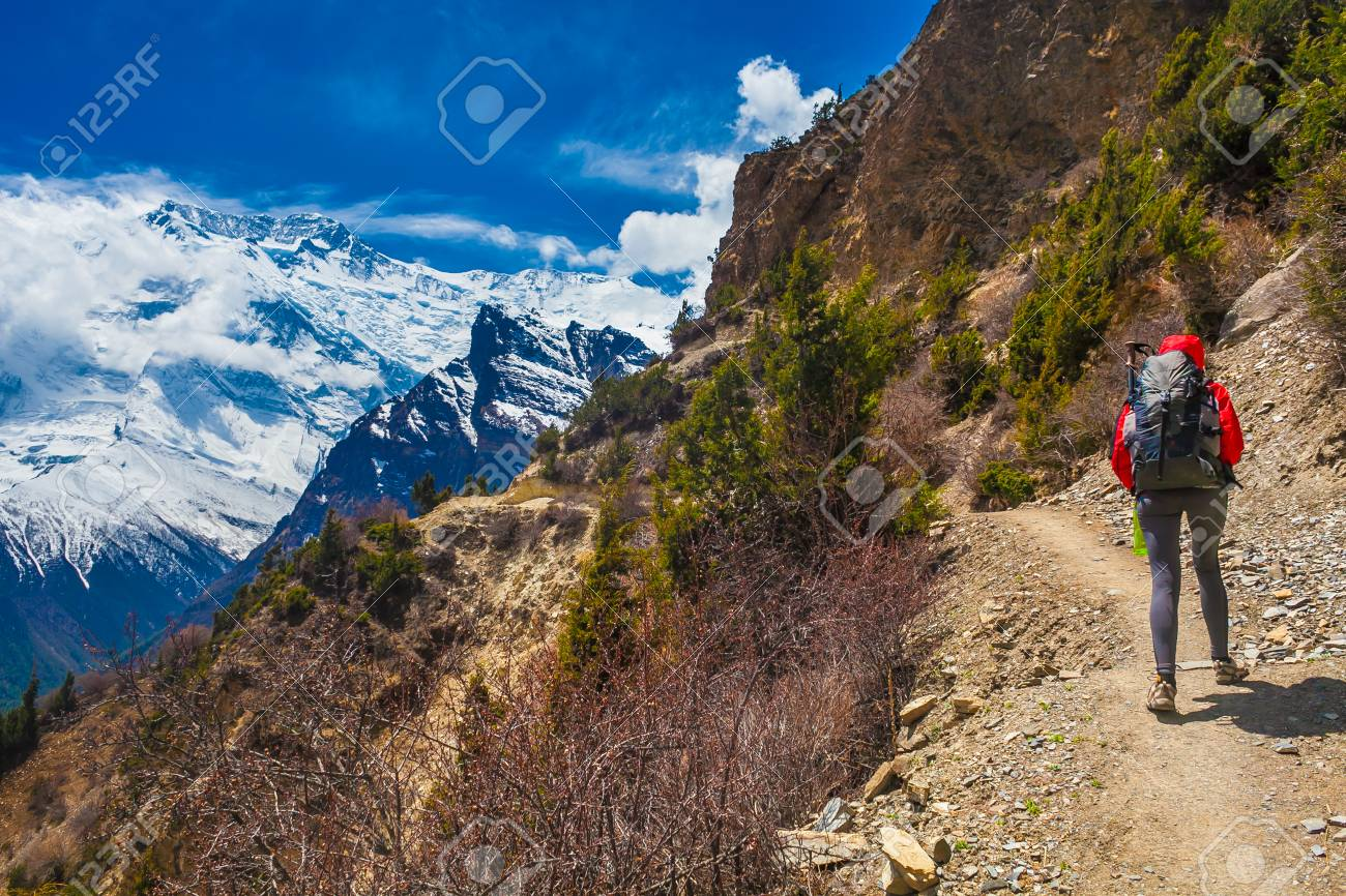 Young Pretty Woman Wearing Red Jacket Backpack Trail Mountains.Mountain Trekking Rocks Path. Snow Landscape View Background. Horizontal Photo Stock Photo - 63727215
