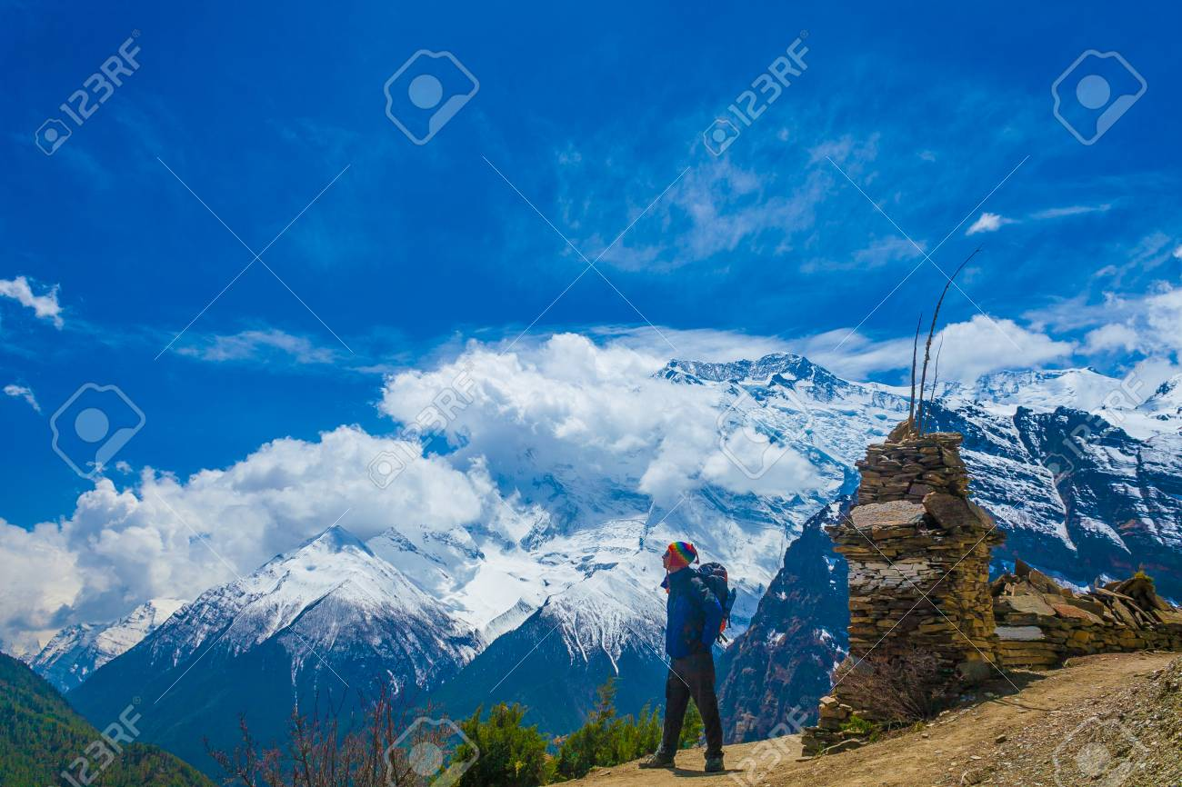 Photo Man Traveler Backpacker Mountains Way.Young Guy Looking Away Take Rest Sunny Terrace Path.Snow Landscape Background. Horizontal Stock Photo - 63727217