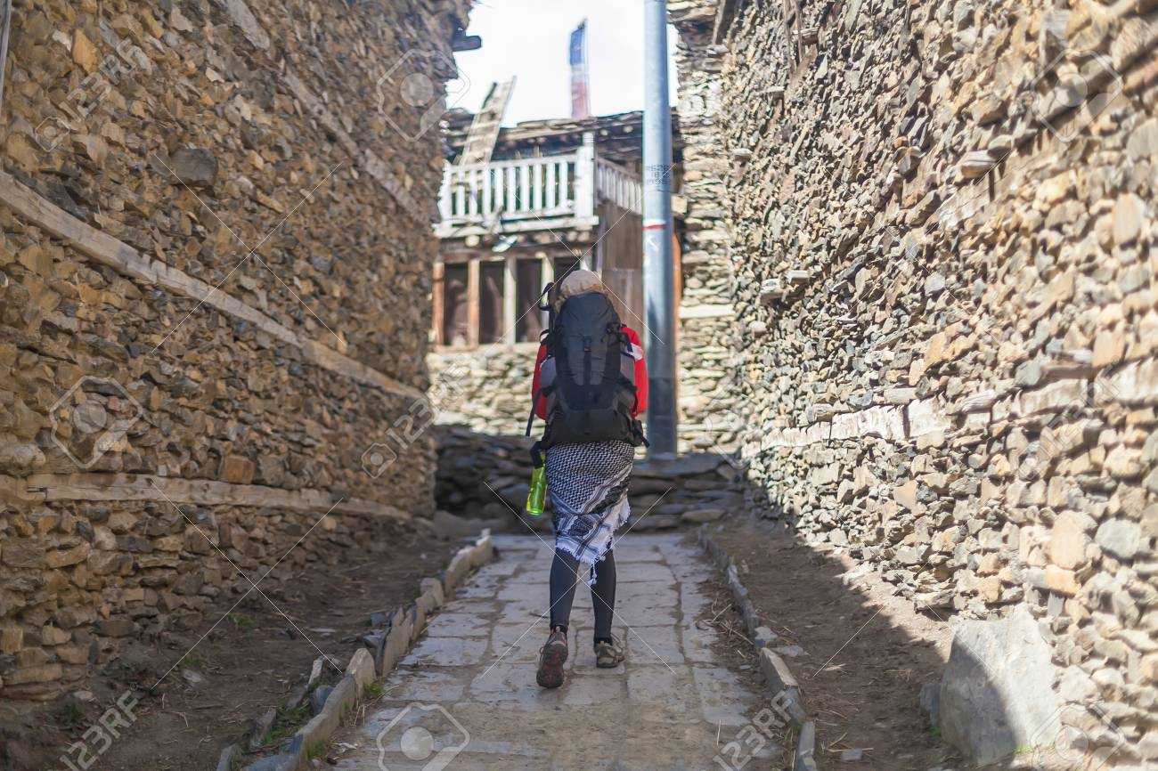 Young Pretty Woman Wearing Red Jacket Backpack Crossing Mountains Village.Mountain Trekking Rocks Path.Old Town Background. Horizontal Photo Stock Photo - 63727326