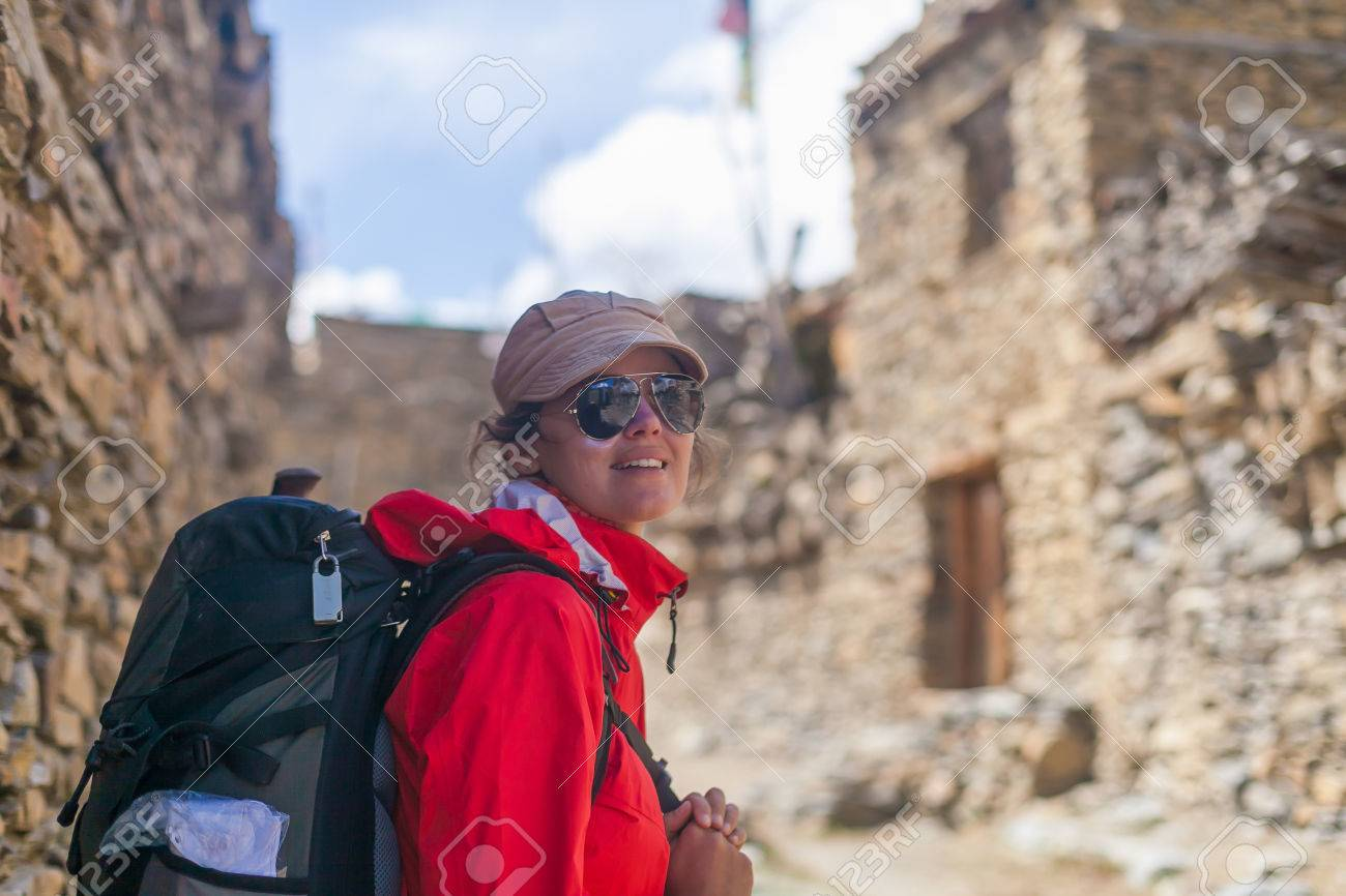 Portrait Young Pretty Woman Wearing Red Jacket Backpack Crossing Mountains Village.Mountain Trekking Rocks Path.Old Town Background. Horizontal Photo Stock Photo - 63727325