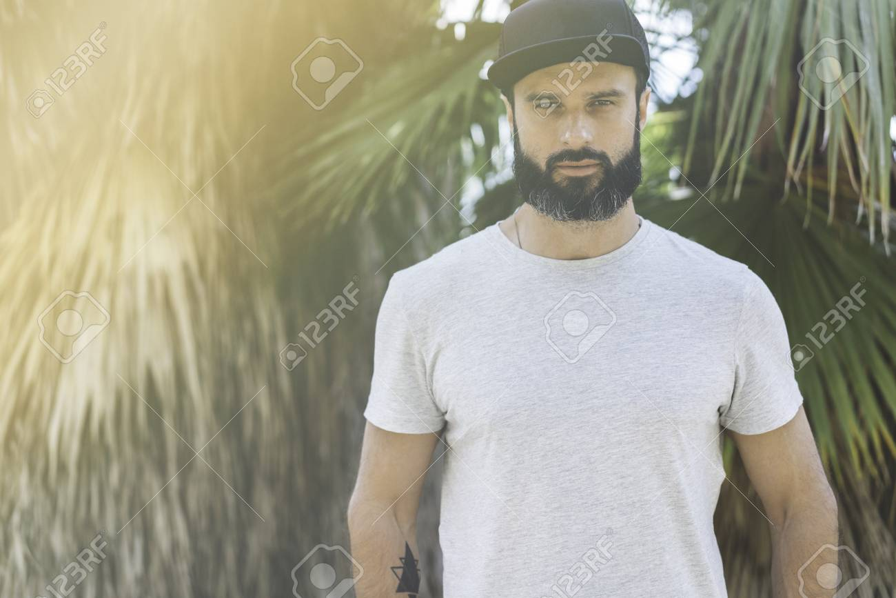 863d088cab1 Hipster handsome male model with beard wearing gray blank t-shirt and a  black snapback