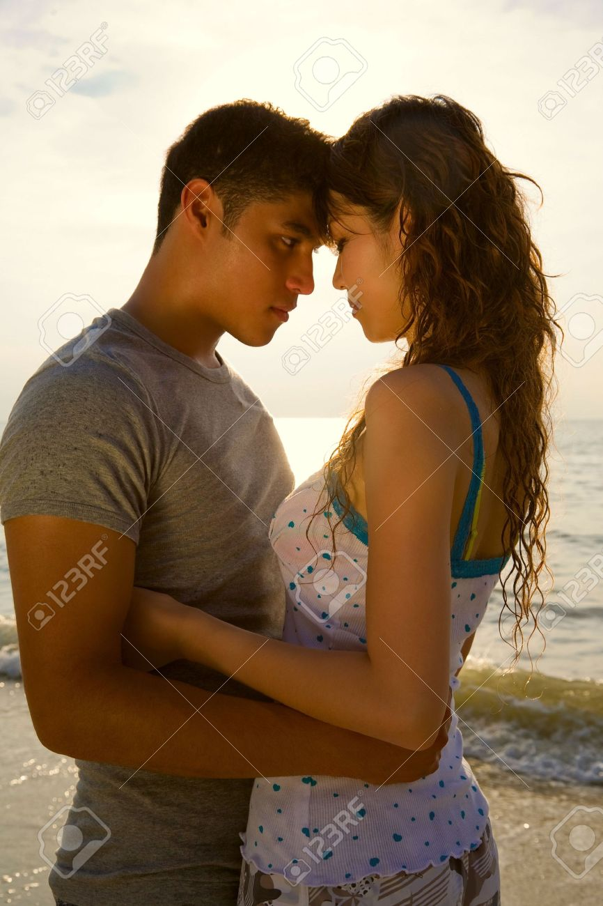 Loving Couple Hugging Each Other At The Romantic Sunset Beach