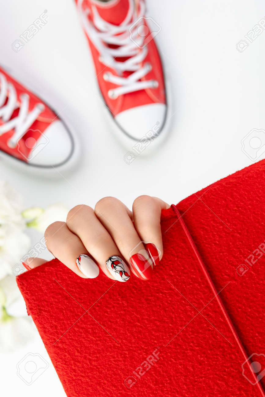 Beautiful young womans hand with red manicure on gray background - 169158665