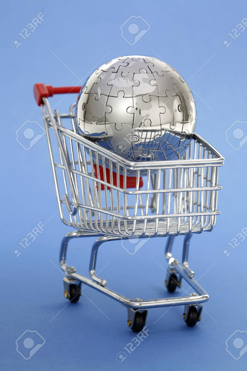 Metal puzzle globe with shopping cart on blue background Stock Photo - 8824067