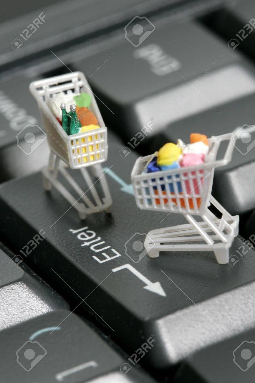 Miniature shopping carts on a computer keyboard Stock Photo - 9510324