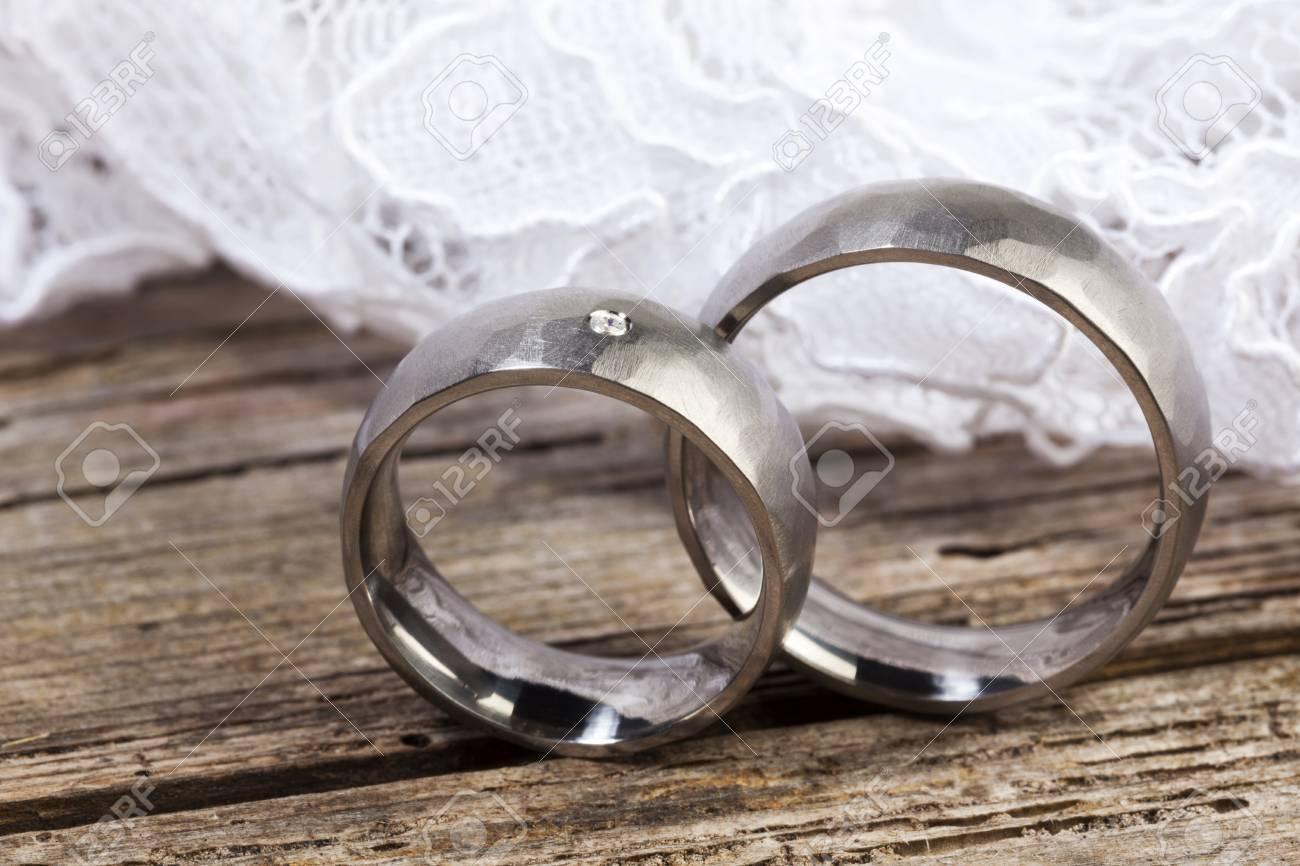 Gros Plan Des Anneaux De Mariage Dargent Et De La Dentelle Sur La Table En Bois