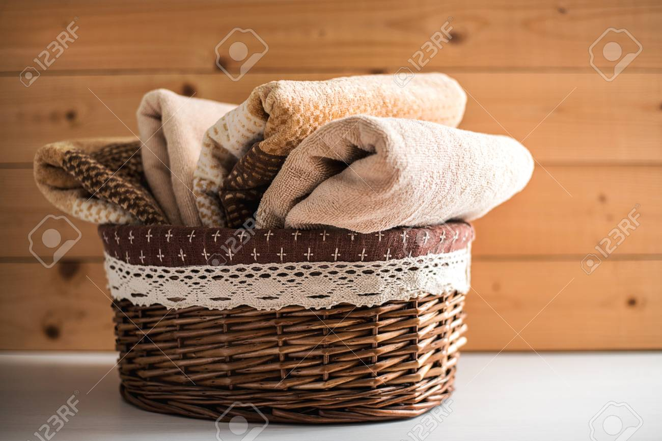 Basket with soft bath towels on wooden background. - 120321092