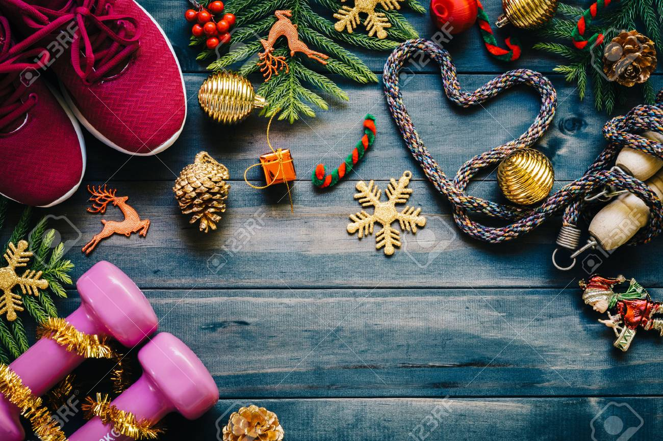 Fitness, healthy and active lifestyles love concept, dumbbells, sport shoes, skipping rope or jump rope in heart shape with Christmas decoration items on wood background. Exercise, Fitness and Working Out Merry Christmas and Happy new year concept. - 88284917
