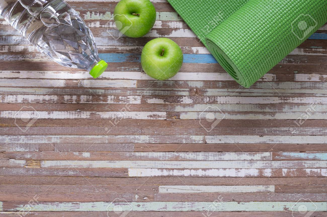 4e32d00c0f6af Active healthy lifestyle background concept. Green yoga mat on a wooden  background with green apples and bottle of water. Active