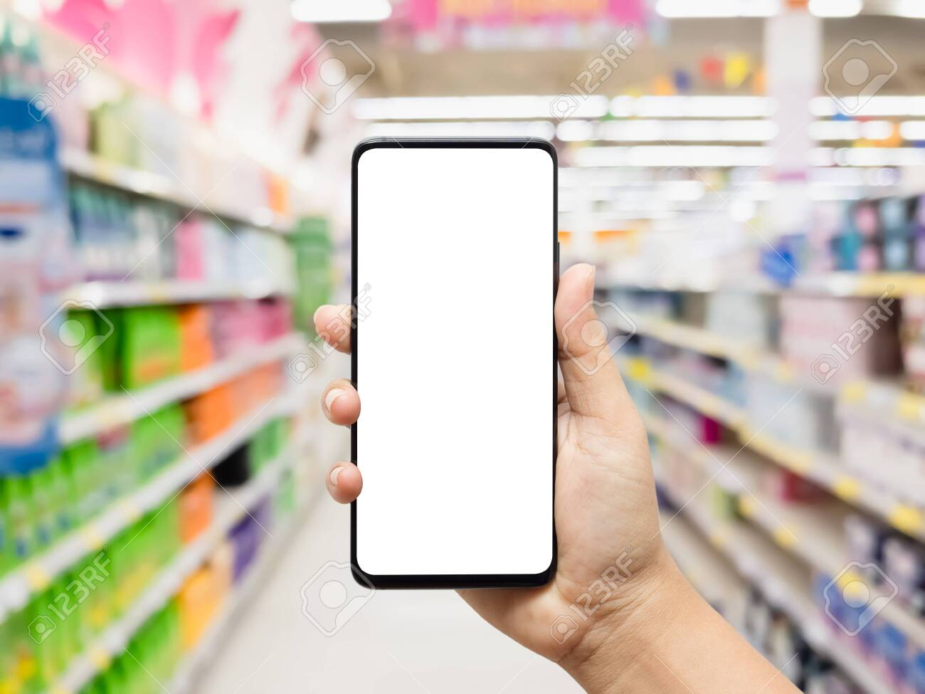 Hand holding smartphone with blurred supermarket - 147019938