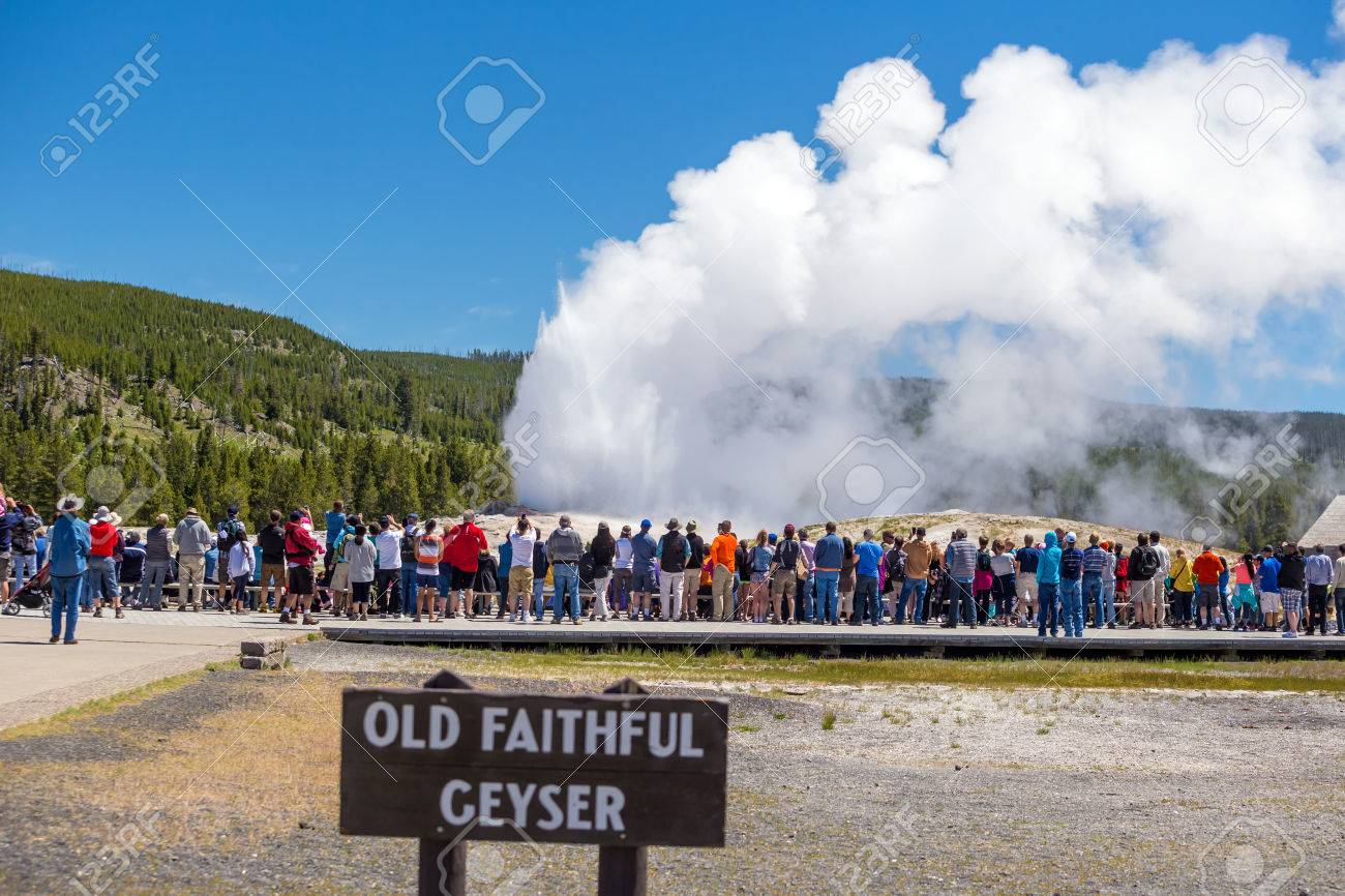 Tourists watching the Old Faithful erupting in Yellowstone National