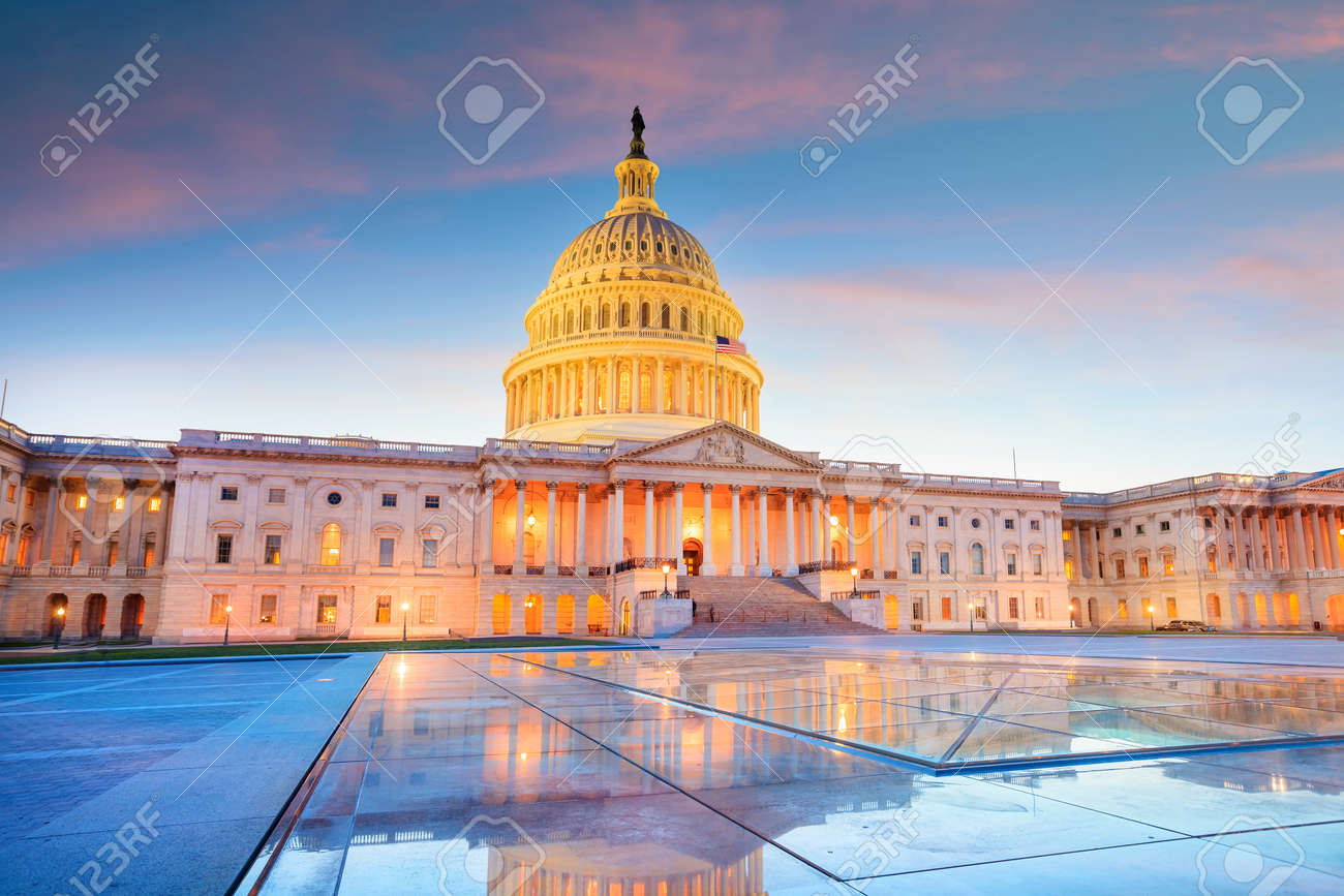 The United States Capitol building with the dome lit up at night. - 155659673