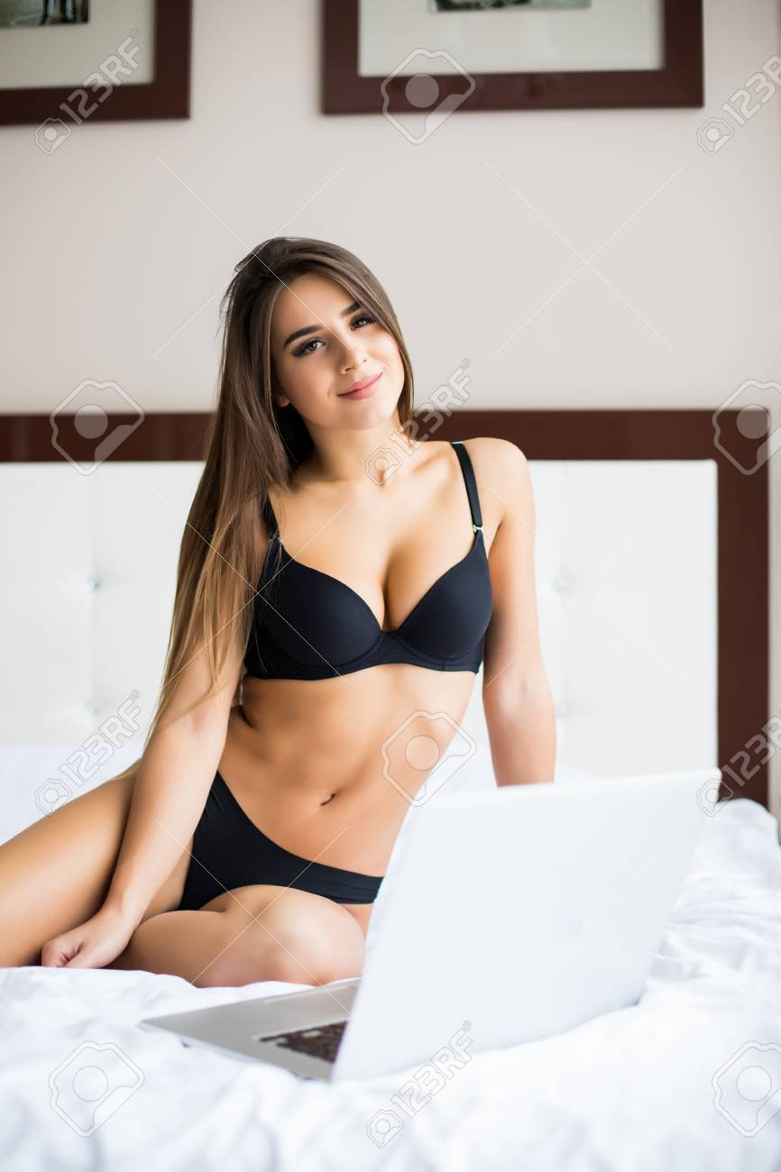 13ee40cd891e Beautiful young girl in black underwear with laptop in bed at home Stock  Photo - 66418167