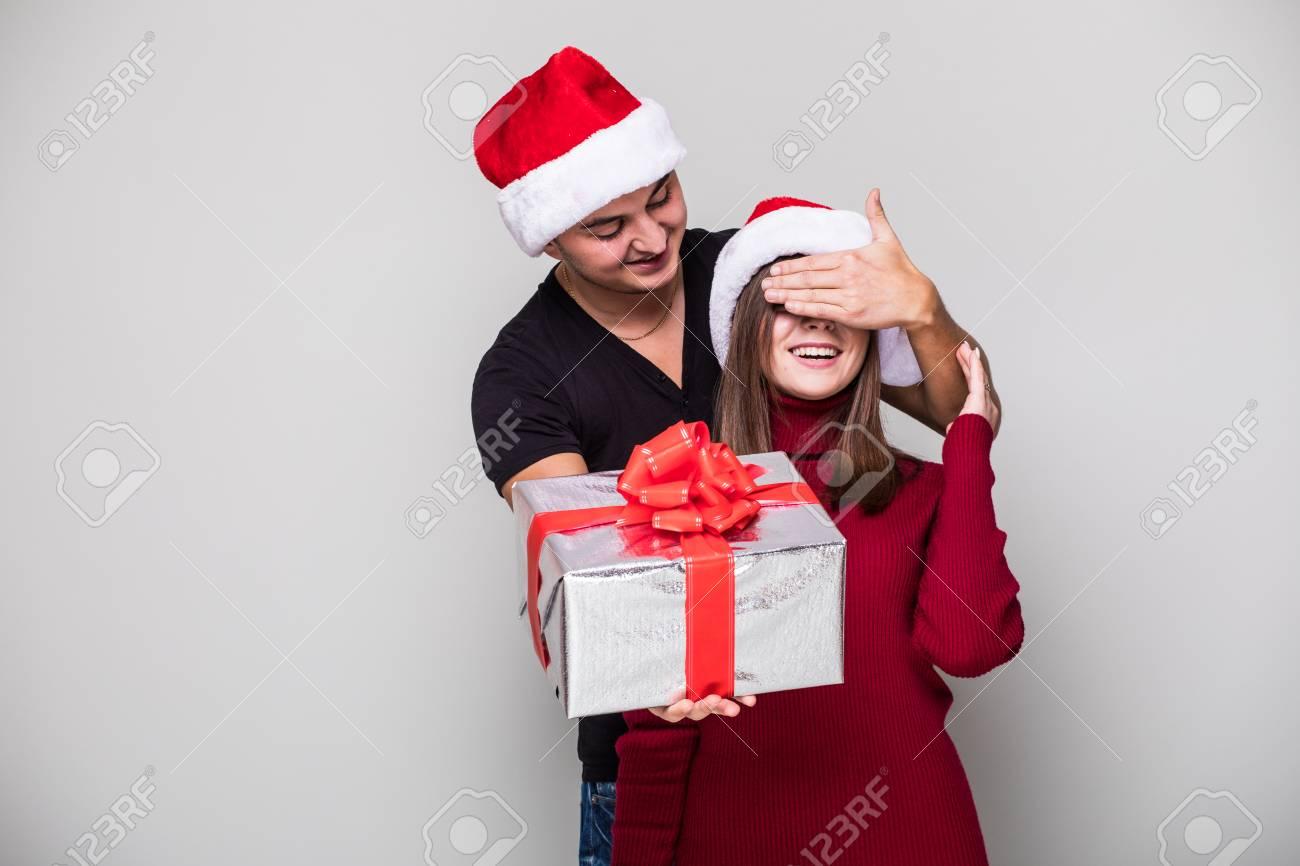 b3dfd2bd423eb Apuesto joven sosteniendo una caja de regalo mientras su novia detrás de él  y cubriendo sus