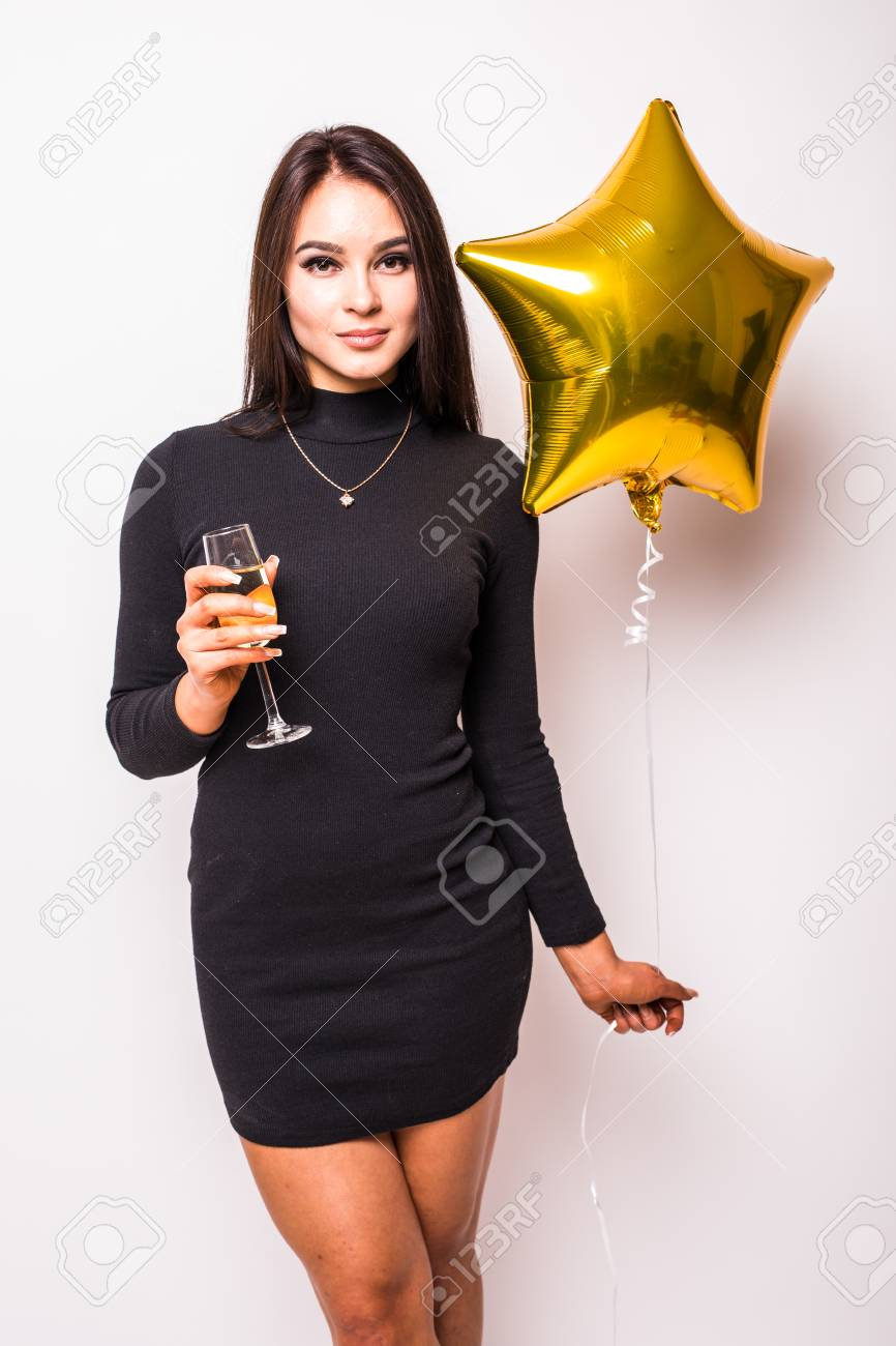 29fe64c2c517 Pretty young woman in black dress with gold star shaped balloon smiling and drinking  champagne over
