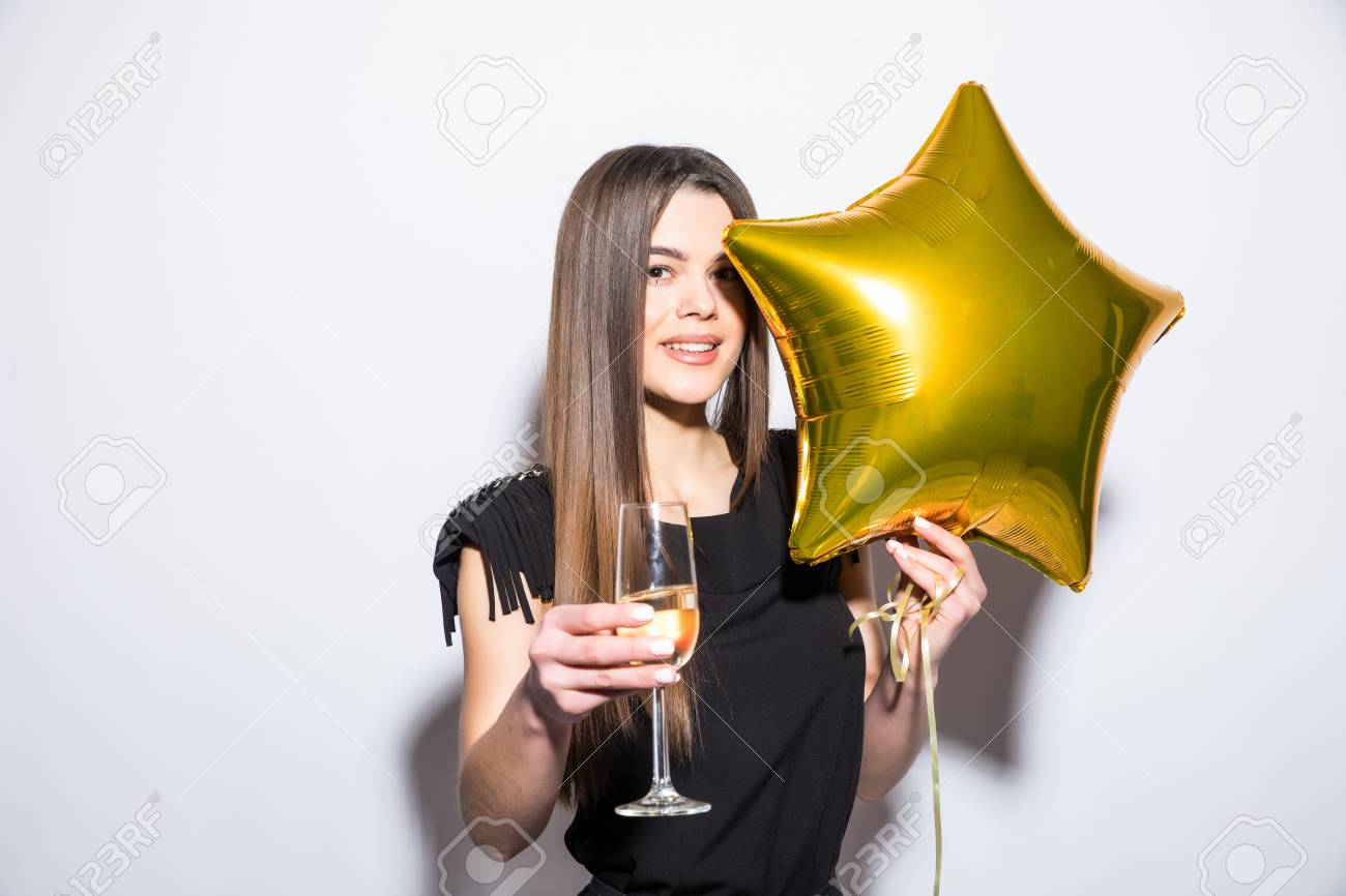 0af473a0ecae Happy attractive young woman in black dress holding star shaped balloon and drinking  champagne over white