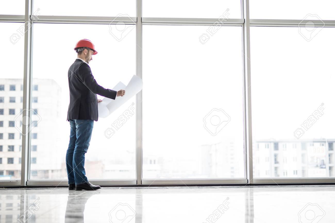 Silhouette builder engineer wear security helmet look at blueprint silhouette builder engineer wear security helmet look at blueprint paper construction near panoramic windows foto de malvernweather Gallery