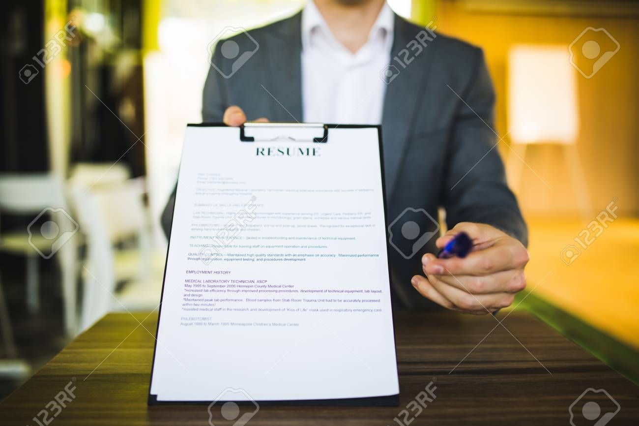 Young businessman submitting resume to employer to review - job