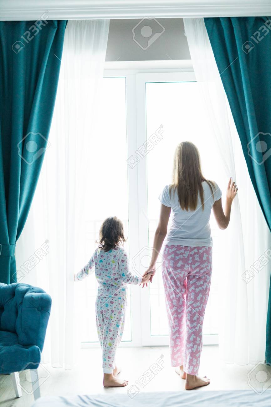 Young Mother With Daughter Opening Window Curtains In Cozy Bedroom Stock Photo Picture And Royalty Free Image Image 93409130